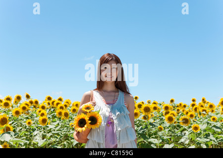Young Woman in Sunflower Field - Stock Photo