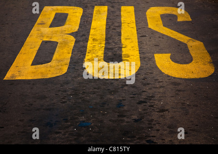 Yellow Bus Stop sign painted on the asphalt - Stock Photo