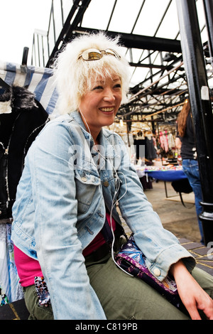 London Camden Town Lock Stables market pretty young Asian Oriental girl female woman with dyed blond hair sitting - Stock Photo