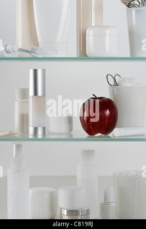 Medicine cabinet full of skincare products and a red apple - Stock Photo