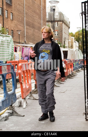London Camden Town pregnant blond woman lady walking past road works wearing Little Mr Naughty t shirt jumper tracksuit - Stock Photo