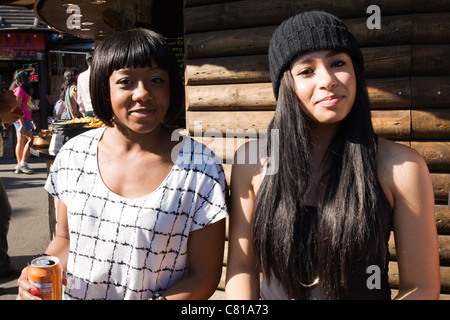 London Camden Town Lock Stables Village market pretty young smiling mixed race girls sitting drinking from can black - Stock Photo