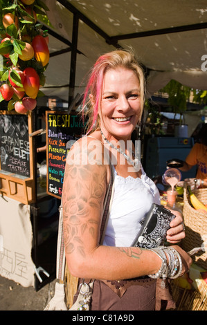 London Camden Town Lock Stables market smiling pretty young blond & pink haired woman lady female tattoos - Stock Photo