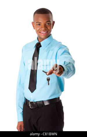 Happy corporate business man realtor handing over keys to new house, dressed in blue shirt and black tie, isolated. - Stock Photo
