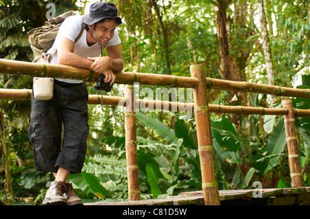 Hispanic man with backpack standing on wooden walkway - Stock Photo