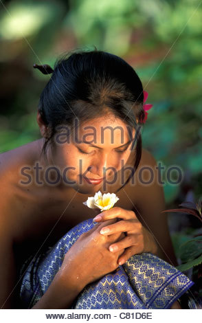 Thai woman smelling flower - Stock Photo
