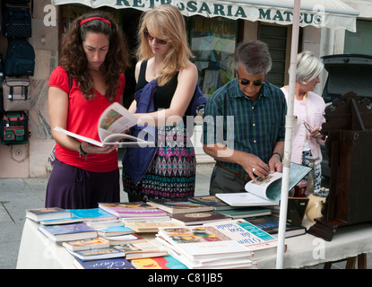 People inspecting books at a flea market, held on the last Saturday of the month, in Praça do Comércio, Coimbra, - Stock Photo