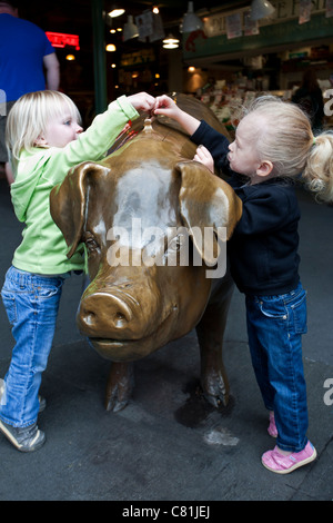Girls putting coins inside a bronze piggy bank (this is the unofficial mascot of the market). Pike Place Market. - Stock Photo