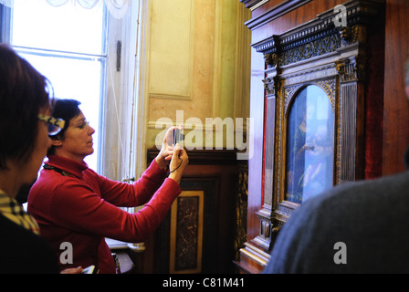Tourist taking photo of Benois Madonna by Leonardo da Vinci, Hermitage Museum, St. Petersburg, Russia - Stock Photo