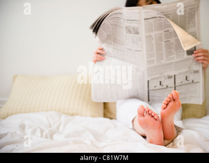 Korean woman reading newspaper in bed - Stock Photo