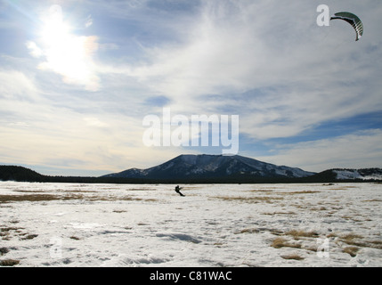 a man snow kiting on a large field with distant mountains - Stock Photo