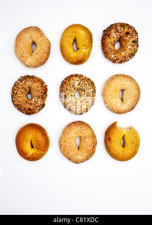Various bagels, one with bite missing - Stock Photo