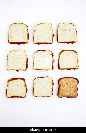 Peanut butter and jelly sandwiches, one on whole wheat bread - Stock Photo