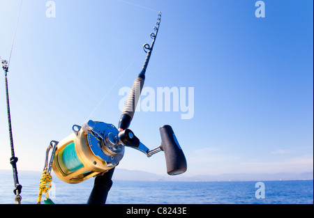 fishing boat trolling in ocean with golden reel rod - Stock Photo