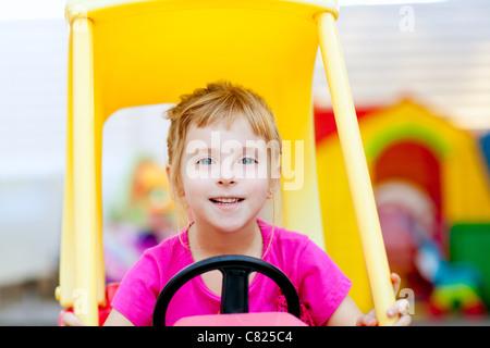 blond children girl driving toy car yellow - Stock Photo