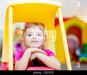 blond children girl resting driving toy car outdoor - Stock Photo