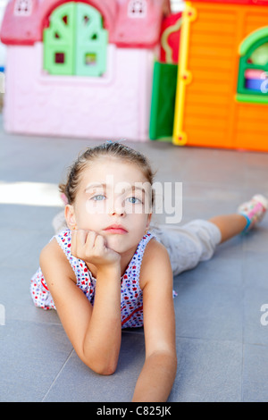 beautiful little serious girl lying on floor in playground - Stock Photo
