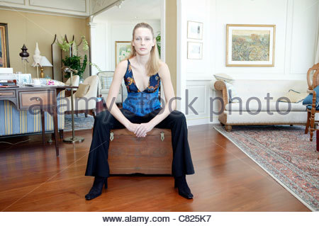 Woman sitting on wooden chest (no property release) - Stock Photo