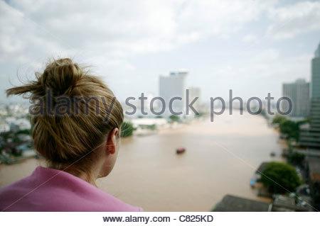 Woman watching skyline of Bangkok, Chao Praya River, Thailand - Stock Photo