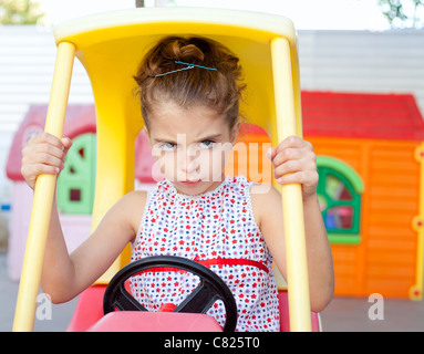 Angry toy car driver children girl in playground - Stock Photo