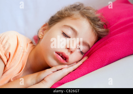 Deep sleeping children girl closeup portrait on pink pillow - Stock Photo