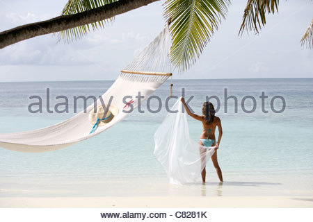 Woman with pareu standing by hammock - Stock Photo