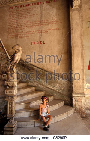 Cuba, Havana, Old town. Girl sitting on stairs under statement of Castro - Stock Photo