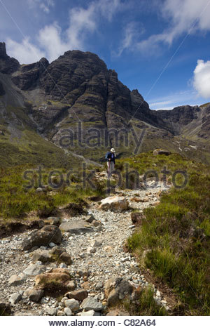 Hillwalker on the path descending from Blaven range in the Black Cuillin mountains on the Isle of Skye, Scotland, - Stock Photo