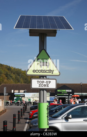 Ecotricity free solar powered charging point for recharging electric battery powered vehicles in motorway services - Stock Photo