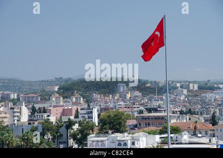 Turkey, Southern Aegean Sea, port city of Kusadasi. Turkish flag flying over Kusadasi. - Stock Photo