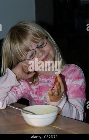 Little Blond Girl wearing a pink shirt admiring a strawberry - Stock Photo