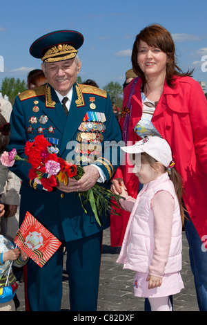 Russian Major General gets flowers on Victory Day from a mother and child at Victory Park in Moscow, Russia - Stock Photo