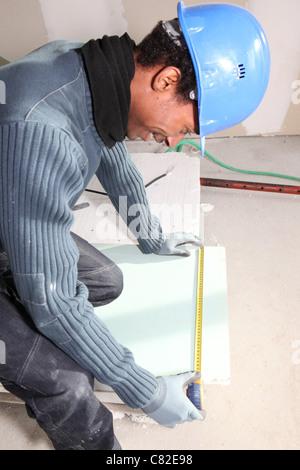 Man measuring plasterboard - Stock Photo