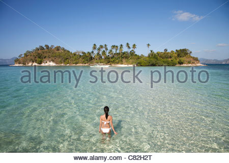 Philippines, El Nido bay,Snake Island,rear view of a woman at sea standing in shallow water. - Stock Photo