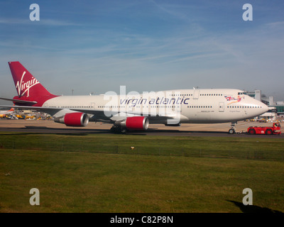 Air travel and the environment. Virgin Atlantic Airways Boeing 747-400 at Gatwick Airport under tow as an alternative - Stock Photo