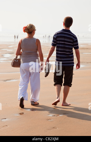 Young couple walking on sandy beach, man barefoot with trousers rolled up carrying shoes at low tide. Cornwall England - Stock Photo
