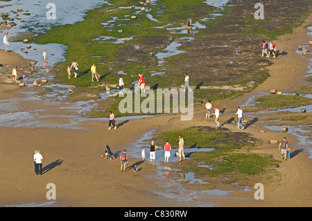 People and young families enjoying the exposed rock pools and sand at the beach at Robin Hoods bay in Yorkshire, - Stock Photo