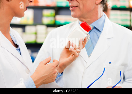 Two pharmacists with pharmaceuticals in hand consulting each other in a pharmacy - Stock Photo