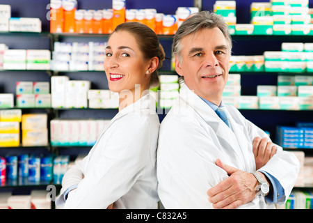 Two Pharmacists standing in pharmacy or drugstore in front of shelves with pharmaceuticals - Stock Photo