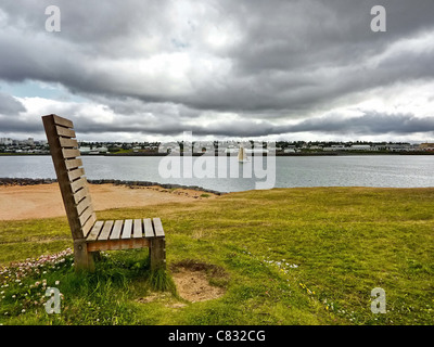 Wooden bench set in green field near a river on cloudy sky - Stock Photo