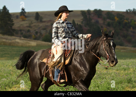 Cowgirl on a black horse riding by - Stock Photo