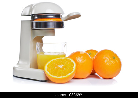 Photo of a juicer and a glass of freshly squeezed orange juice, isolated on a white background. - Stock Photo