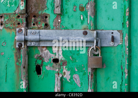Old green wooden door with large bolt and padlock. - Stock Photo
