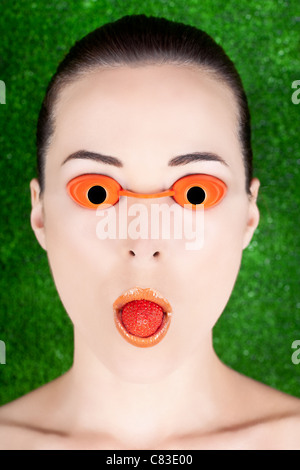 Closeup portrait of a woman wearing tanning bed glasses with strawberry in mouth against green - Stock Photo