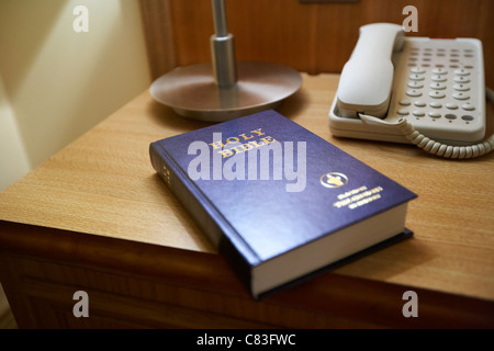 holy bible placed by the gideons on the beside table in the interior of a 4 star hotel bedroom - Stock Photo