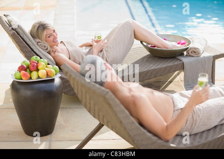 Couple relaxing in lawn chairs by pool - Stock Photo