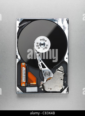 Open computer hard disk drive HDD isolated on metallic background - Stock Photo