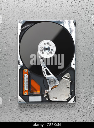 Open computer hard disk drive HDD on wet metal surface - Stock Photo