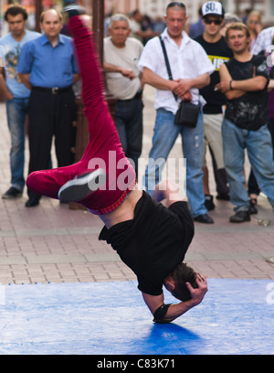 A young man shows his ability to dance upside down in the Arbat street in Moscow, Russia - Stock Photo