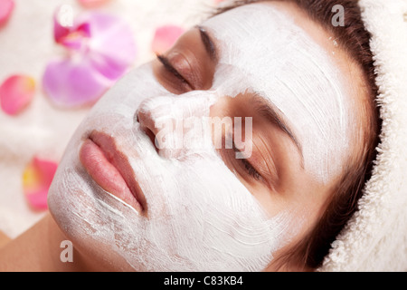 Young woman with cosmetic mask on her face. - Stock Photo